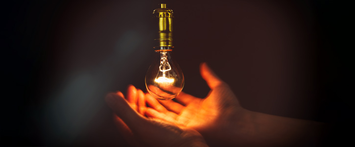 Hands cradling a light bulb